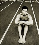 Young man sitting on track