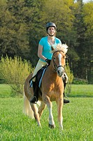 young woman riding on Haflinger horse