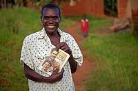 man showing a religious book, Burundi, Makamba, Makamba