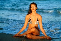 Young woman sitting in yoga position on beach