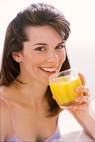 Woman drinking glass of orange juice