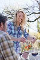 Woman serving boyfriend salad outdoors