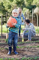 Boy carrying gourd in garden