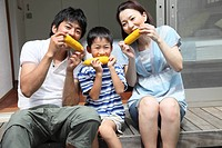 Family eating corn at verandah