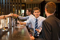 Businessmen having drinks at bar