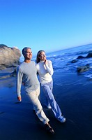 Mature Couple Walking at Rocky Coast
