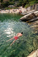 Young adult swimming relaxed in Cala D'en Serra, Ibiza, Spain