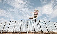 Athlete jumping over fence