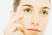 Woman applying undereye cream, close_up