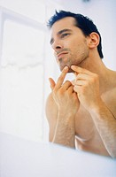 Unshaven man in the bathroom ckecking spot on chin in the mirror