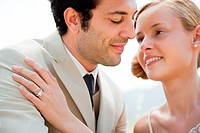 Bride wearing wedding ring with hand on groom's shoulder (thumbnail)