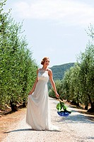 Bride on country road holding bouquet (thumbnail)