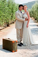 Newlyweds on country road with suitcase