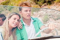 Young couple driving convertible car (thumbnail)