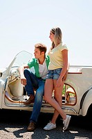 Young couple by convertible car looking away