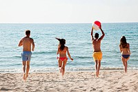 Four people playing with beach ball on beach