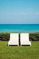 Two empty white sun loungers on grass (thumbnail)