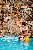Young couple embracing and kissing in swimming pool