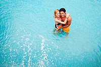 Young couple embracing in swimming pool, high angle