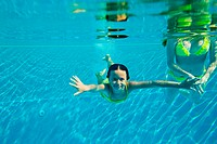 Woman with girl swimming in swimming pool, underwater view