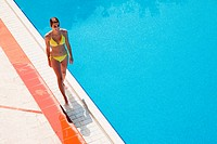 Young woman walking by poolside