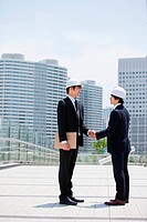Two businessmen wearing hard hats, shaking hands