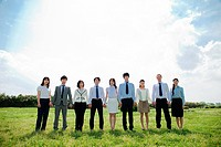 Businesspeople in a row in field, holding hands (thumbnail)