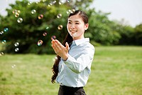 Portrait of young businesswoman touching bubbles