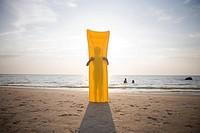 Girl standing behind an air mattress, Grand Beach, Manitoba