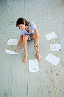 Woman sitting on decking with financial documents