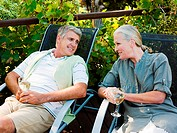 Couple sitting on garden chairs with wine