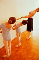 Young ballet teacher teaching two little girls
