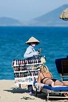 Conical hat woman selling sunglasses on beach Nha Trang resort Vietnam