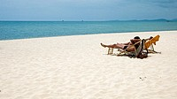 Couple relax in deck chairs on white sand Long Beach Phu Quoc Island Vietnam
