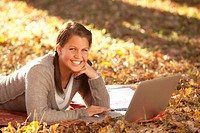 Caucasian teenager using laptop on ground