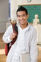 Hispanic teenage boy standing in classroom