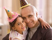 Grandfather and granddaughter in party hats