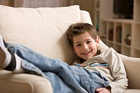 Smiling Caucasian boy sitting in armchair
