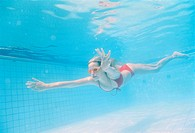 Young woman diving, swimming pool