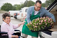Florist helping customer in wheelchair load flowers into car