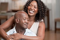 Laughing African American woman hugging husband