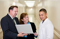 Business people and doctor looking at laptop in hospital corridor