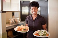 African American waitress carrying food on plates