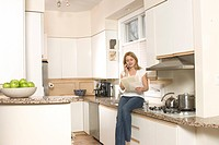 Woman Reading Letter on Phone in Kitchen