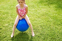 Young Girl Sitting on Bouncy Ball
