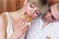 Young Couple, She Eating a Hamburger