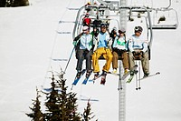 Skiers Sitting on Chair Lift