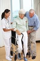 Nurse and Senior Man Helping Senior Woman to Stand