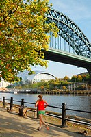 Woman jogging along Quayside under The Tyne bridge  Gateshead Sage concert hall in distance  Newcastle upon Tyne, England, United Kingdom