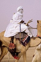 In-Gall, near Agadez, Niger  Tuareg Man Riding Camel, with Camel Saddle and Decorations Visible  Man rides bare foot  Camel has red leather talisman a...